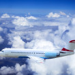 Airplane at fly on the sky with clouds - Stock Photo