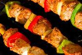 Tres tiro diagonal pinchos de metal con pimientos de carne, cebollas, rojo y verde haciendo souvlaki. — Foto de Stock