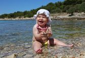 Baby girl playing with pebbles at the Adriatic beach in Croatia — Stock Photo