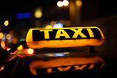 Yellow taxi sign at night — Stock Photo