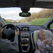 Stock Photo: Mother driving car with baby