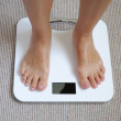 Female feet on bathroom scale — Stock Photo