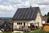 屋根上のソーラー パネルと家 — ストック写真