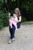 Young mother with daugther on swing — Stock Photo