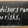 """Advisers run no risks"" written on a blackboard — Stock Photo"