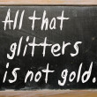 &quot;All that glitters is not gold&quot; written on a blackboard - Stock Photo