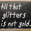 "Stock Photo: ""All that glitters is not gold"" written on blackboard"