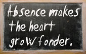 """Absence makes the heart grow fonder"" written on a blackboard — Stock Photo"