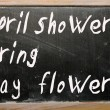 April showers bring May flowers written on a blackboard — Stock Photo