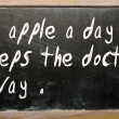 An apple a day keeps the doctor away written on a blackboard — Stockfoto