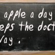 """An apple a day keeps the doctor away"" written on a blackboard — Stock Photo #6642440"