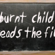 """burnt child dreads fire"" written on blackboard — Stock Photo #6642590"