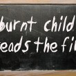 "Stock Photo: ""burnt child dreads fire"" written on blackboard"
