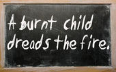 """A burnt child dreads the fire"" written on a blackboard — Stock Photo"