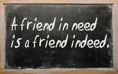 """A friend in need is a friend indeed"" written on a blackboard — ストック写真"