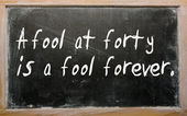 """""""A fool at forty is a fool forever"""" written on a blackboard — Stock Photo"""