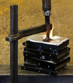 Pressed hard drives with clamp and fire — Stock Photo