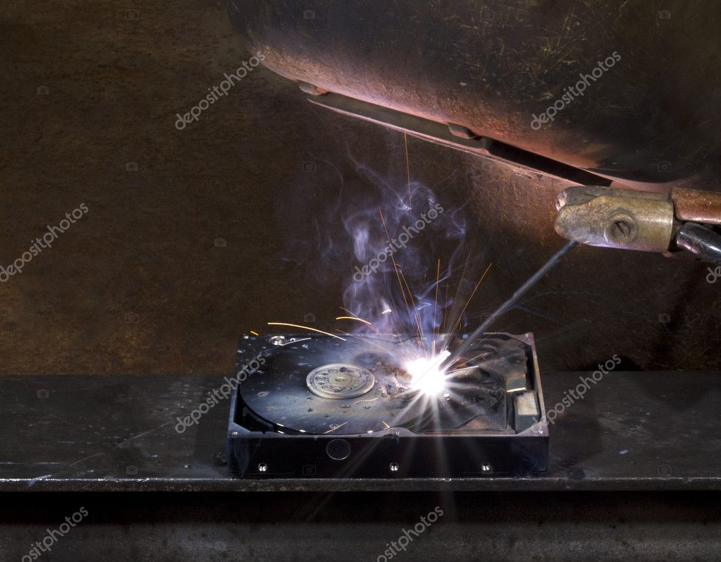 Repairing a defect hard disk with welding apparatus. Protective shield and smoke on rusty background — Stock Photo #6239410