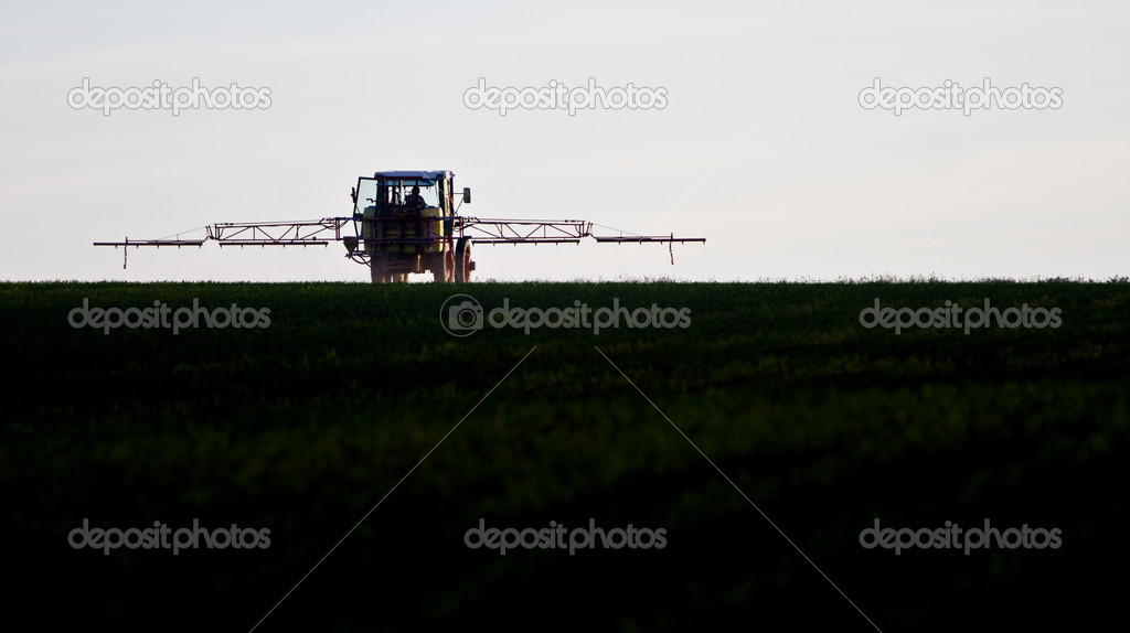 Tractor spraying agricultural pesticide on field — Stock Photo #6259767