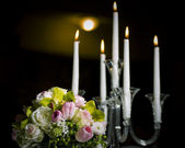 Floral bouquet and candles — Stock Photo