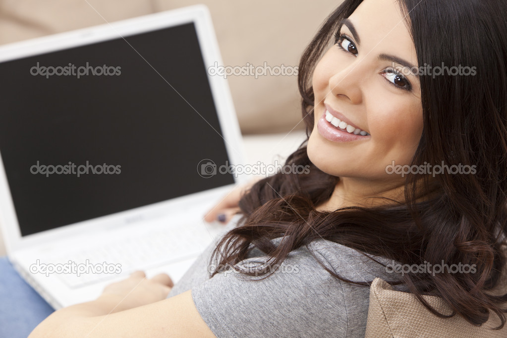 Beautiful happy young Latina Hispanic woman smiling and using a laptop computer at home on her sofa — Stok fotoğraf #6253566