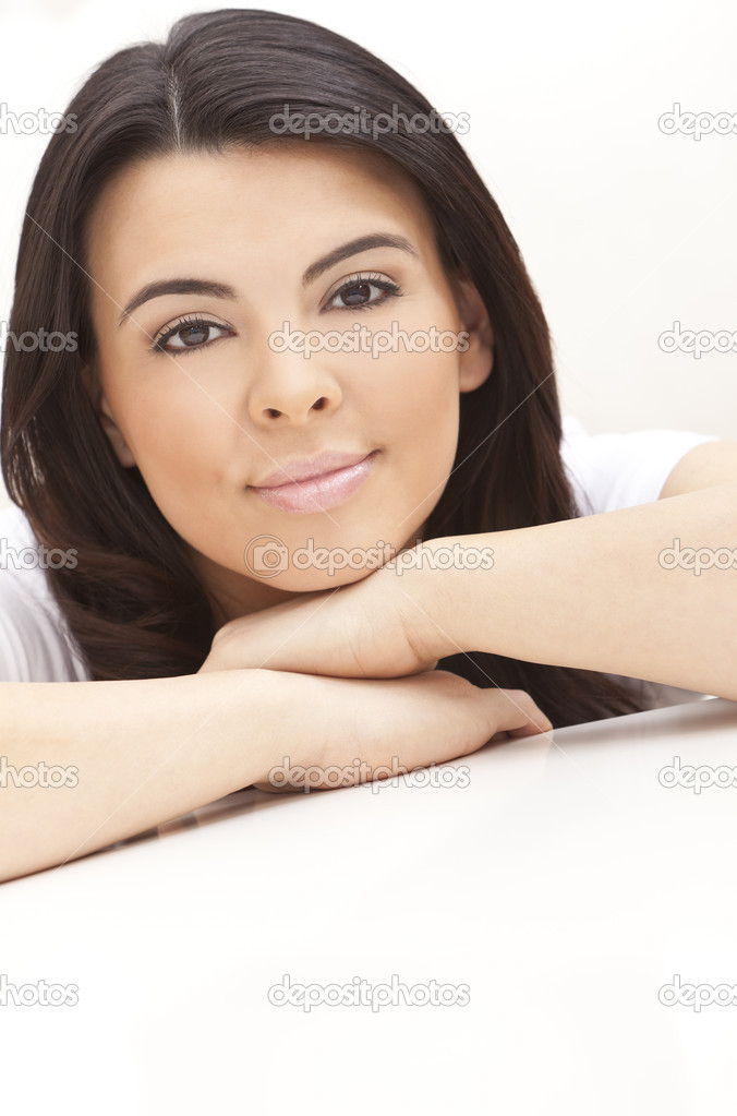 Studio portrait of a beautiful young Latina Hispanic young woman or girl looking thoughtful resting on her hands  Stock Photo #6253577