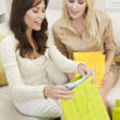 Two Beautiful Women Friends Looking in Shopping Bags at Home - Stock Photo
