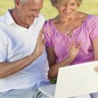 Happy Senior Couple Using Laptop Computer Outside in Sunshine — Stock Photo #6266426
