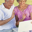 Happy Senior Couple Using Laptop Computer Outside in Sunshine — Stock Photo