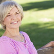 Happy Senior Woman Sitting Outside Smiling — Stock Photo #6266453
