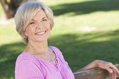 Mujer senior feliz sentado afuera sonriendo — Foto de Stock