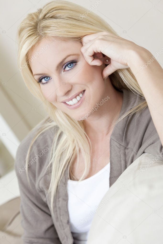 Natural light portrait of a beautiful blond woman with blue eyes resting on her sofa at home — Stock Photo #6266272