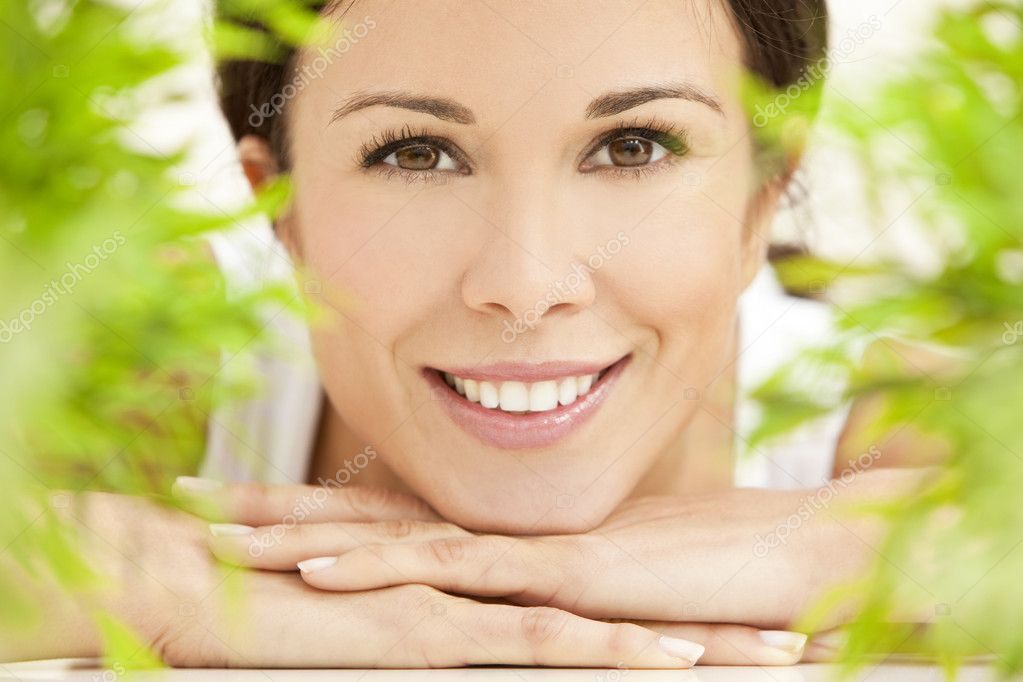 Health spa nature concept studio portrait of a beautiful young woman or girl resting on her hands smiling through natural green leaves — Lizenzfreies Foto #6266332
