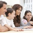 Family Sitting Using Laptop Computer At Home - Stock Photo