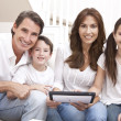 Happy Family Having Fun Using Tablet Computer At Home - Stock Photo