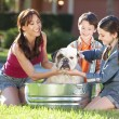 Royalty-Free Stock Photo: Mother Son & Daughter Family Washing Pet Dog In A Tub