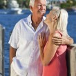 Happy Senior Couple On Vacation By Tropical Sea - Stock Photo