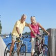 Happy Senior Couple on Bicycles By a River — Stock Photo