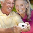 Happy Senior Couple Taking Photograph with Digital Camera — Stock Photo