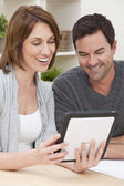Happy Man & Woman Couple Using Tablet Computer at Home — Stockfoto