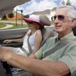 Senior Couple Driving Convertible Car Wearing Sunglasses — Stock Photo