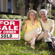 Senior Couple With For Sale Sold By Owner House SIgn - Stock Photo