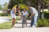 African American Family WIth Boy Riding Bike & Happy Parents — ストック写真