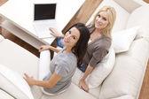 在沙发上使用手提电脑在家里的两个年轻妇女 — 图库照片