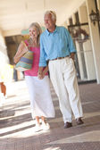 Happy Senior Couple Holding Hands in Shopping Mall — Stock Photo