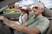 Senior Couple Driving Convertible Car Wearing Sunglasses — Stock Photo