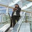 Young Indian Asian Businesswoman On Cell Phone and Escalator - Stok fotoğraf