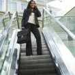 Businesswoman on an Escalator - Stock Photo