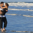 Man Carrying Woman in Romantic Embrace On Beach — Stock Photo