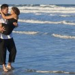 Stock Photo: Man Carrying Woman in Romantic Embrace On Beach